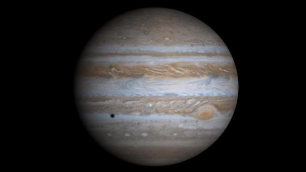 """2000年12月7日由""""卡西尼""""探测器所拍摄的木星照片。照片左下角的黑色斑点是木卫二所投下的影子。版权:NASA。"""